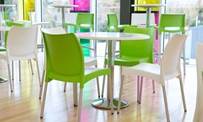 Babatti Chairs In Green And White In A Dining Room With Round White Tables